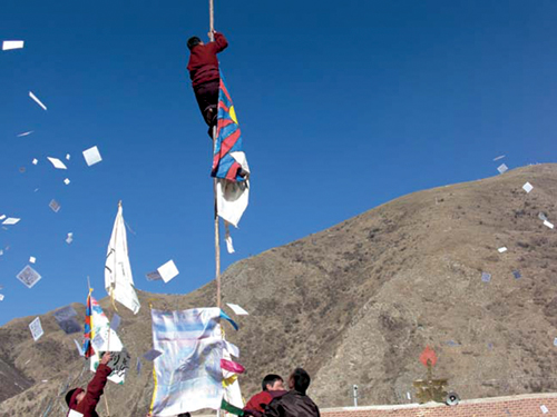 "A monk protestor hoisting the banned Tibetan national flag during a peaceful protest held in Chigdril County, Golog ""TAP"", Qinghai Province, 17 March 2008"