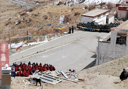 A group of Tibetan monks protesting, sitting on a road were confronted by riot police who cordoned off the entrance to Gaden Monastery, Taktse Country, east of Lhasa, 12 March 2008