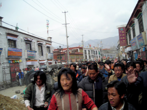 "Spontaneous protest also broke out in several other locations around the city, including the Barkhor area and ""TAR"" Government Headquarter Road. Hundreds of protesting Tibetans ran through the streets waving traditional white scarves in their hands, shouting ""Free Tibet"" and ""The Dalia Lama should return to Tibet"", Lhasa, 14th March 2008"