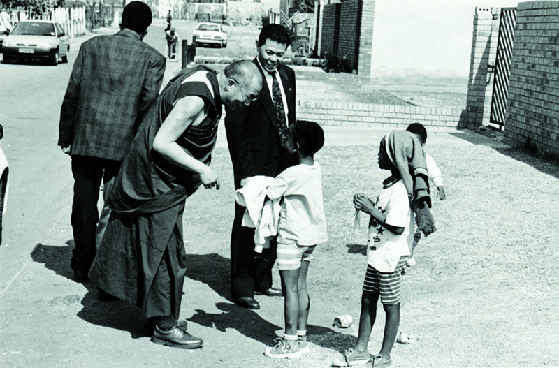 His Holiness the Dalai Lama speaking to African children outside a Sowetan family house, 1996