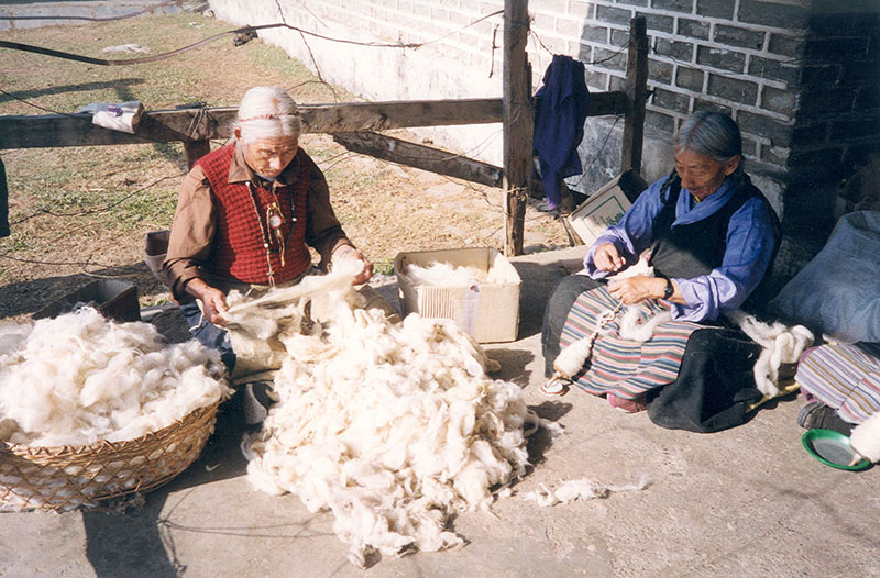 Old aged people spinning wool at Tashi Palkyil Tibetan Settlement in Pokhara, Nepal