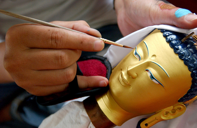 Thangka painter giving finishing touches to the face of a statue of Buddha Shakyamuni at Norbulingka Institute, Dharamshala.