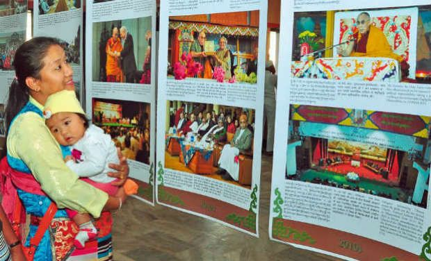 A mother takes a look at the Tibetan photographic exhibition that is being organised in a Coimabatore hotel. —DC