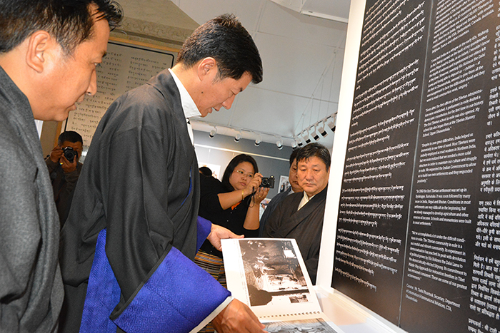 Sikyong watching photo album on Tibetan Community in Exile