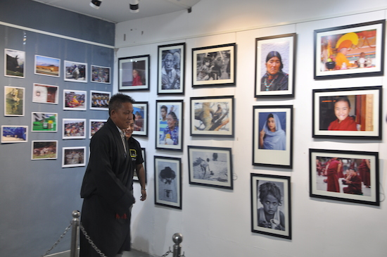 Kalon Karma Yeshi inspecting the exhibition by photographer Kalsang Jigme.