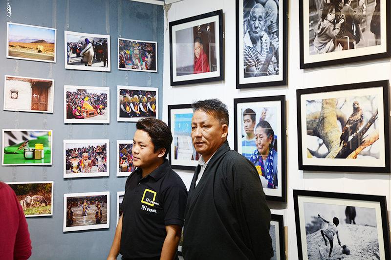 Kalon Karma Yeshi inspecting the exhibition by photographer Kalsang Jigme.