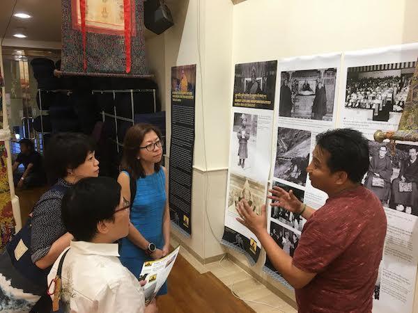 Director Tashi Phuntsok guiding visitors at exhibition at Amitabha Buddhist center