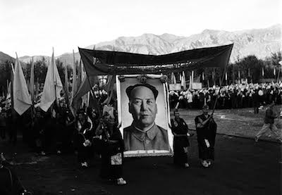 "Two monks with a banner lead a group of monks with a giant portrait of Mao Zedong and flags to celebrate the foundation of the so-called ""Tibet Autonomous Region"" on September 9, 1965. Less than a year later, the monks and nuns became the target of the wrath of violent Red Guards during the Cultural Revolution."