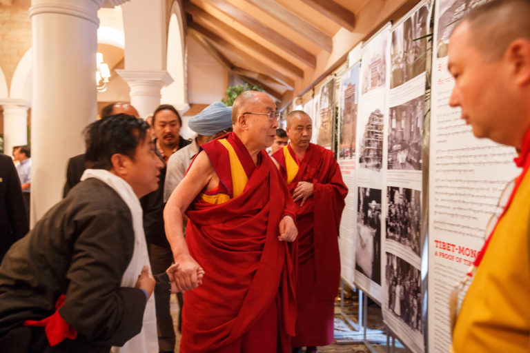His Holiness the Dalai Lama looking at a photo exhibition on display in the meeting room for the dialogue with Russian scientists in New Delhi, India on August 7, 2017. Photo/ArtemSavateev
