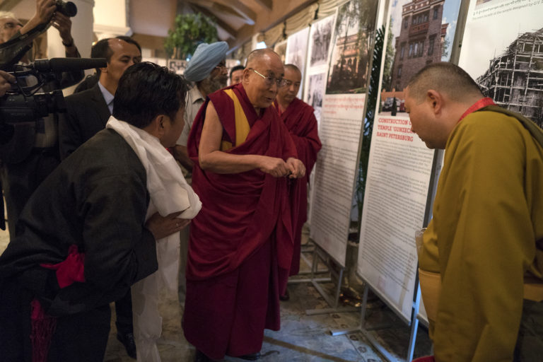 His Holiness the Dalai Lama looking at a photo exhibition on display in the meeting room for the dialogue with Russian scientists in New Delhi, India on August 7, 2017. Photo/TenzinChoejor/OHHDL