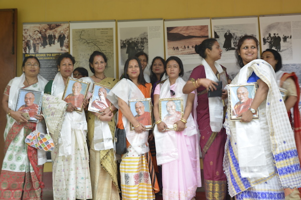 Visitors to the exhibition holding photos of His Holiness the Dalai Lama.